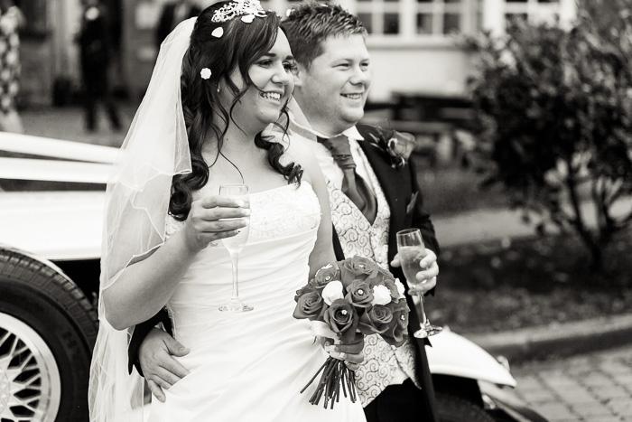 Bride and groom by wedding car