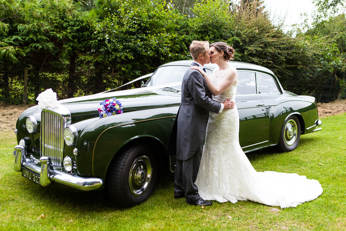 Bride & Groom Kissing by wedding car