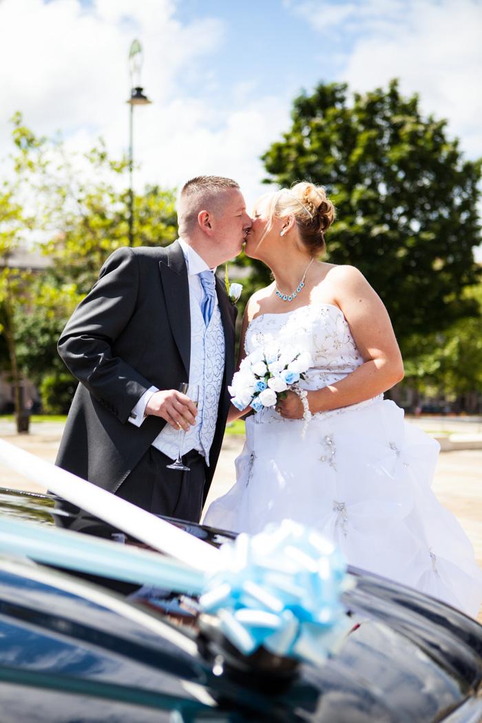 Bride & groom kissing in wedding car