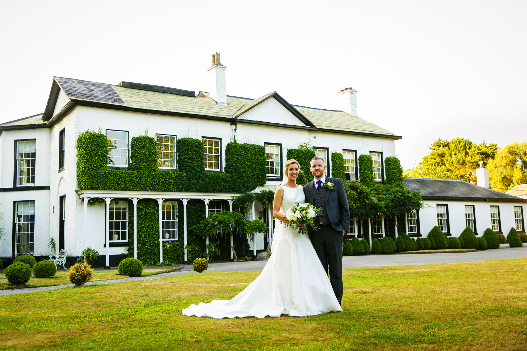 Bride and groom in front of Statham Lodge wedding