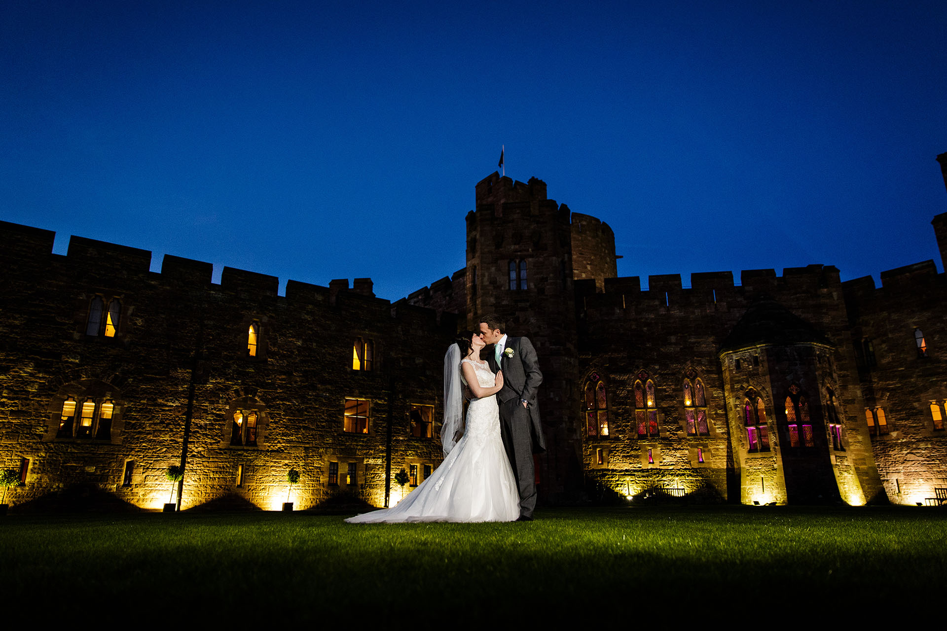 bride and groom kissing in front of peckforton castle i
