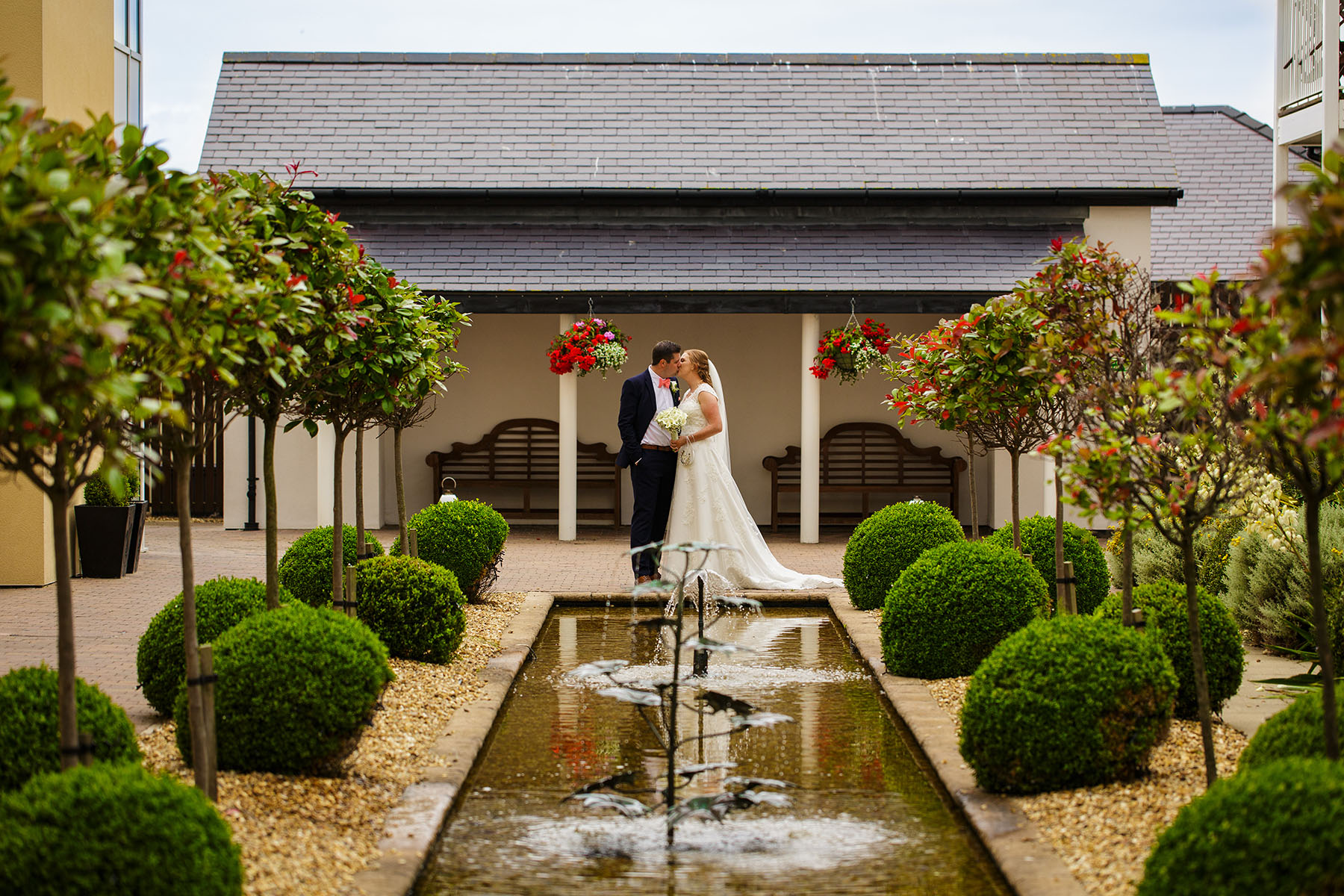 Bride and groom portrait near water feature